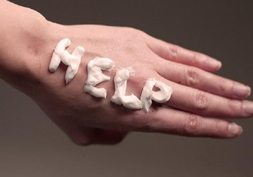 надпись help кремом на руке